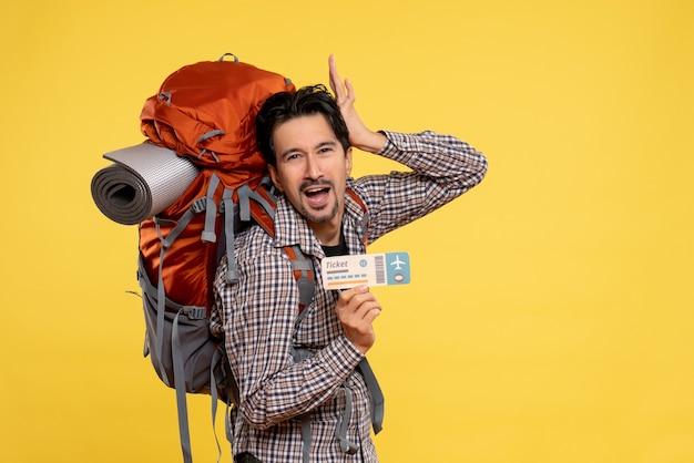 黄色の飛行機のチケットを保持しているバックパックと正面図の若い男性