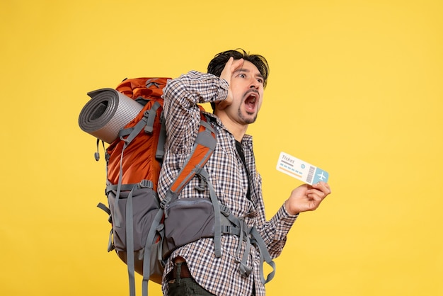 Front view young male with backpack holding ticket screaming on yellow