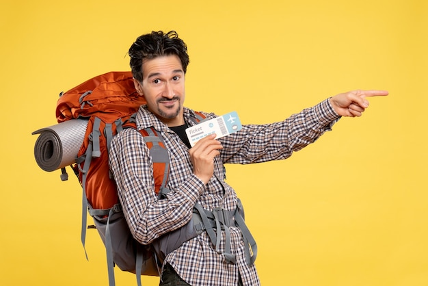 Front view young male with backpack holding ticket on a yellow