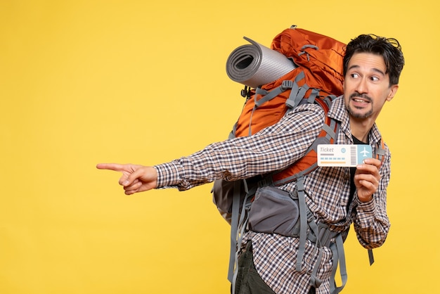 Front view young male with backpack holding ticket on yellow