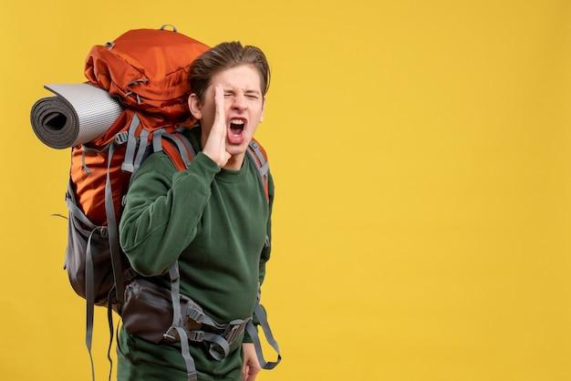 ハイキングと電話の準備をしているバックパックを持つ若い男性の正面図