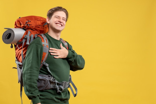 ハイキングの準備をするバックパックを持つ若い男性の正面図