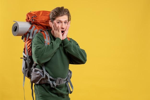 Giovane maschio di vista frontale con lo zaino che si prepara per l'escursionismo