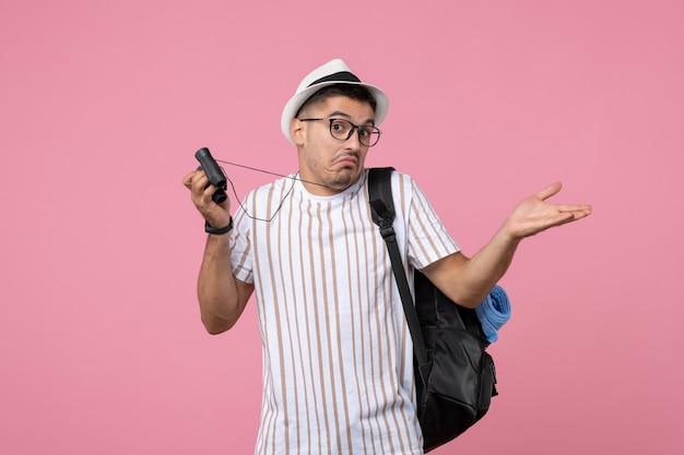 Вид спереди молодой мужчина с сумкой и биноклем на розовом фоне