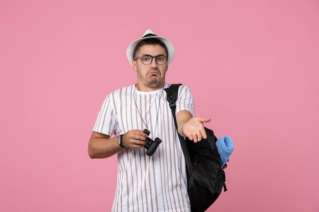 Vista frontale giovane maschio con borsa e binocolo sullo sfondo rosa