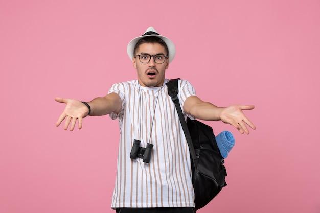 Vista frontale giovane maschio con borsa e binocolo su occhi maschili con vista a colori del pavimento rosa