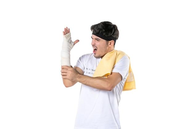 Вид спереди молодой мужчина с повязкой на раненой руке на белом фоне подходит тренажерный зал спортсмен йога образ жизни спорт тело диета