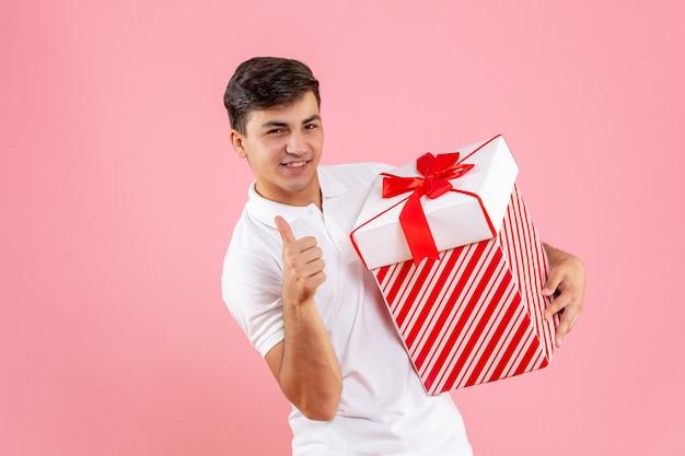 ピンクの背景に大きなクリスマスプレゼントと正面図若い男性