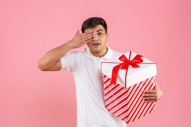 분홍색 배경에 큰 크리스마스 선물 전면보기 젊은 남성