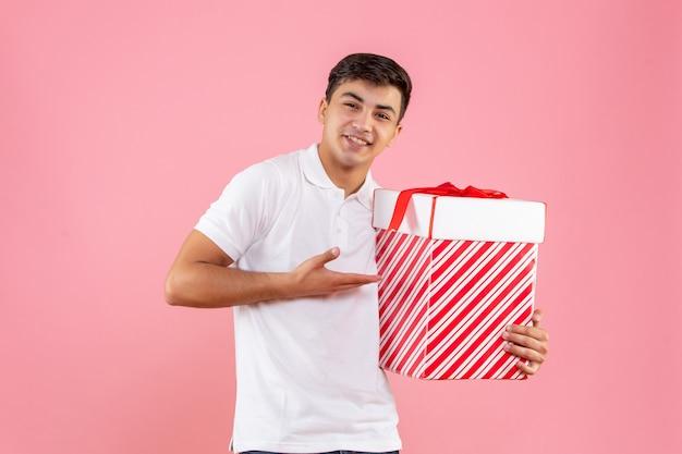 Giovane maschio di vista frontale con grande regalo di natale su fondo rosa