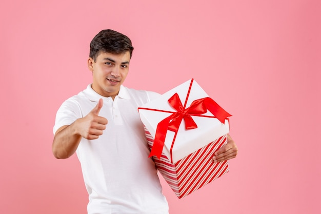 Front view young male with big christmas present on pink background