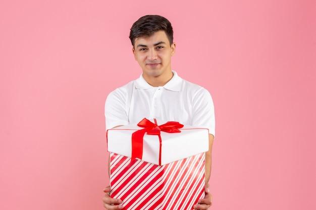 Vista frontale giovane maschio con grande regalo di natale sorridente su sfondo rosa