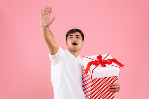 Giovane maschio di vista frontale con grande regalo di natale che fluttua su fondo rosa