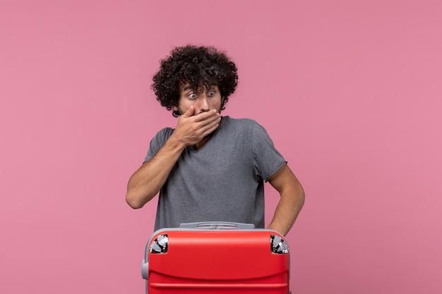 旅行の準備とピンクのスペースでポーズをとって大きな赤いバッグを持つ若い男性の正面図