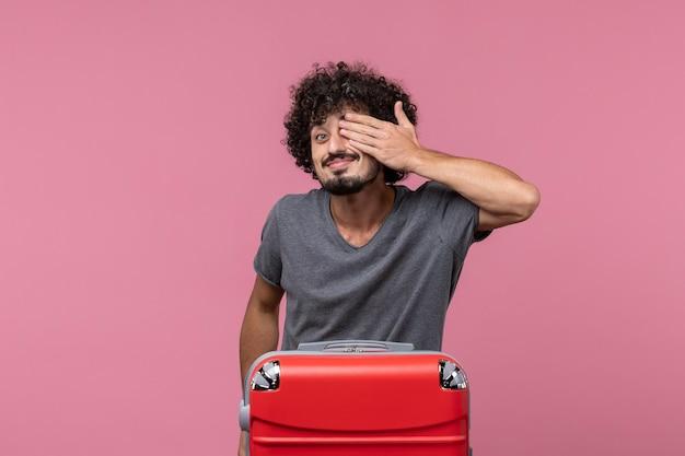 ピンクの空間で旅行の準備をしている大きな赤いバッグを持つ正面図若い男性