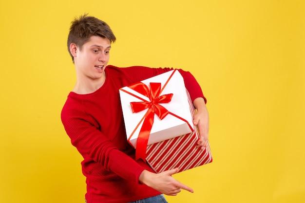 Вид спереди молодой самец с большим рождественским подарком на желтом фоне