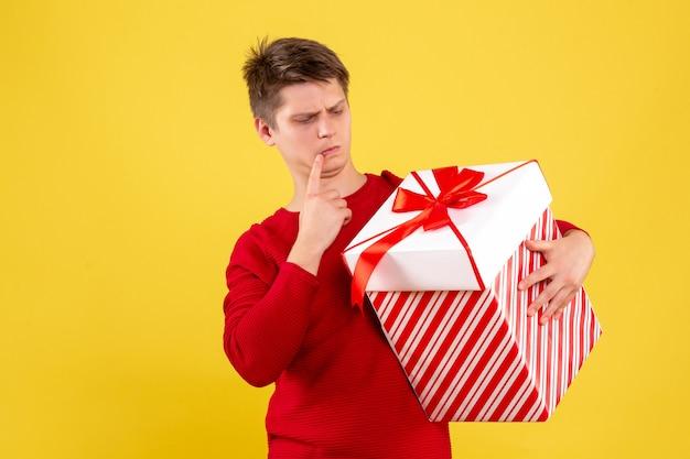 黄色の背景に存在する大きなクリスマスの正面図若い男性