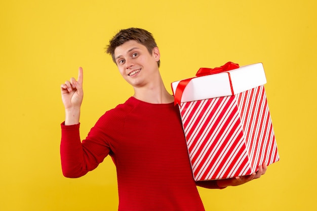 Front view young male with big xmas present on yellow background