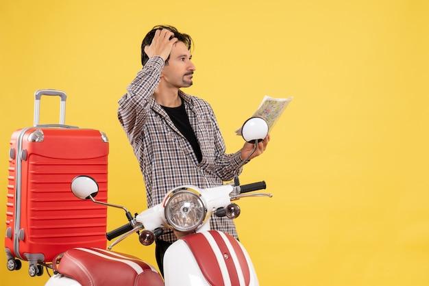 Вид спереди молодой самец с велосипедом, держащий карту на желтом