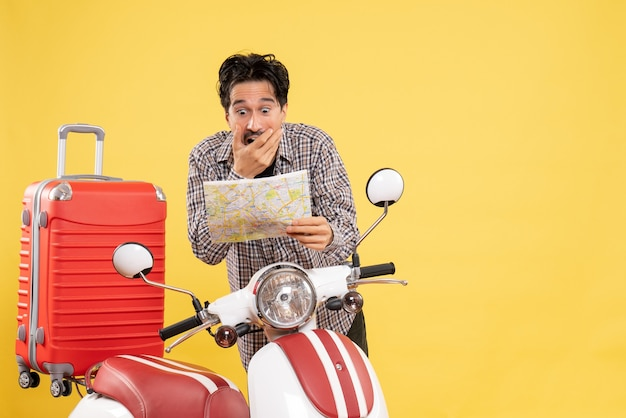 Front view young male with bike observing map with shocked expression on yellow