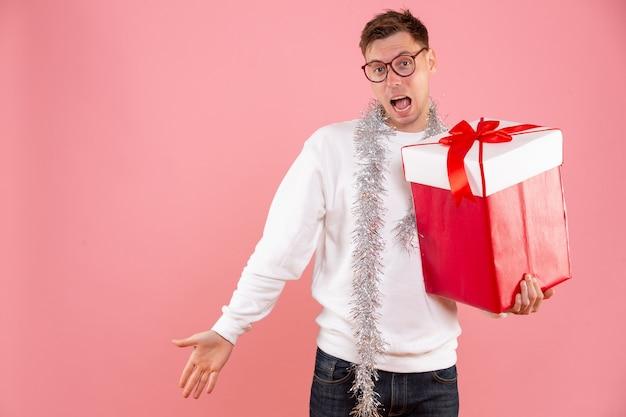ピンクの背景にクリスマスプレゼントと正面図若い男性