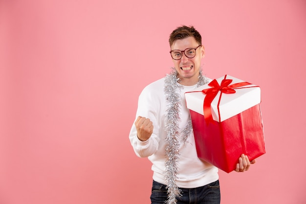 Giovane maschio vista frontale con regalo di natale su sfondo rosa