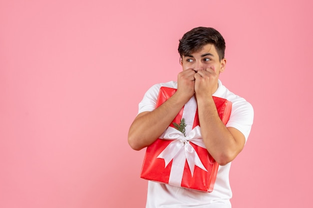 Vista frontale giovane maschio con regalo di natale spaventato su sfondo rosa