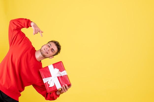 Вид спереди молодой самец с рождественским подарком