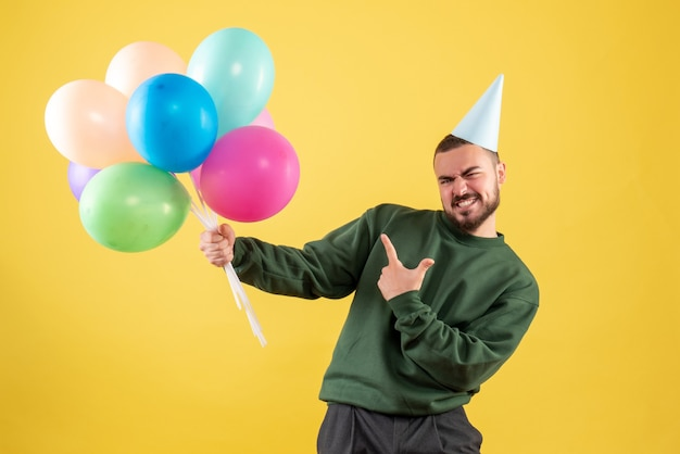 Front view young male with colorful balloons on the yellow background