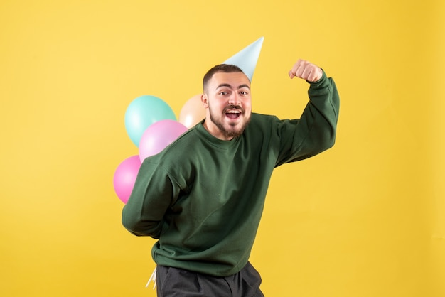 Front view young male with colorful balloons on yellow background