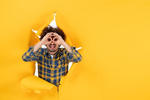 黄色の破れた背景に巻き毛の若い男性の正面図