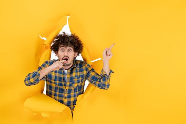 노란색 찢어진 배경에 곱슬 머리를 가진 전면보기 젊은 남성