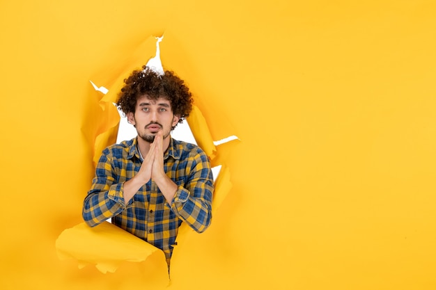 前视图:卷发的年轻男性在黄色背景上祈祷