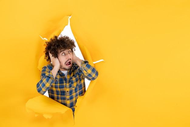 前视图:在黄色背景下,一头卷发的年轻男性