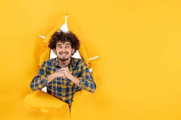 正面图:一头卷发的年轻男性在黄色背景下微笑
