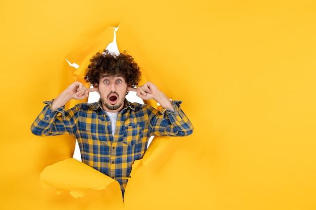 正面图:一头卷发的年轻男性,在黄色撕破的背景上,耳朵嘎嘎作响