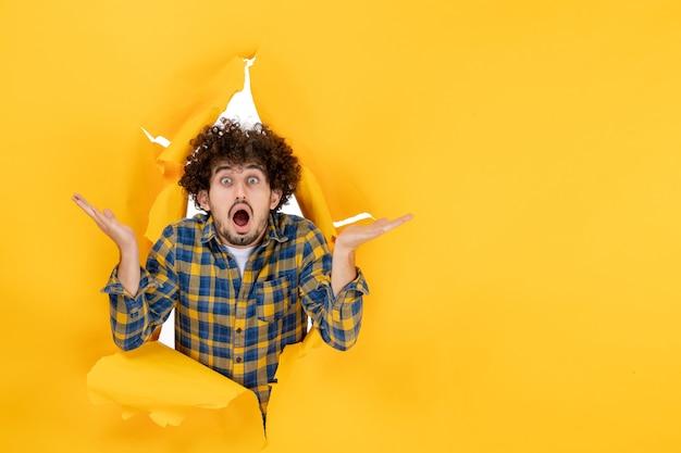 正面图:一头卷发的年轻男性,在黄色的背景上惊讶不已