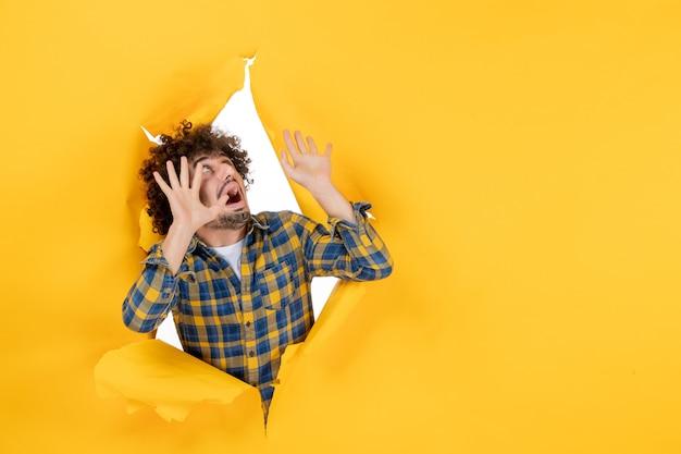 黄色の破れた背景に怖い顔で巻き毛の若い男性の正面図