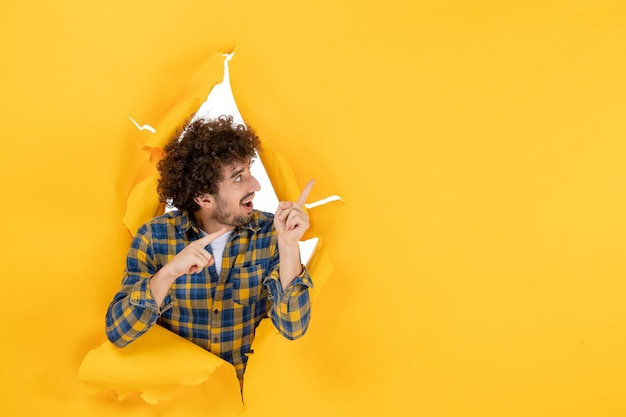 Front view young male with curly hair on yellow ripped background