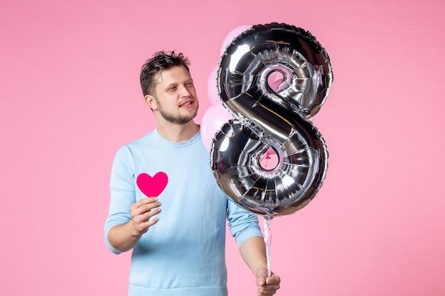 Вид спереди молодой мужчина с милыми воздушными шарами и сердечком на розовом фоне любовь женский день дата равенства мартовский парк чувственное женское веселье