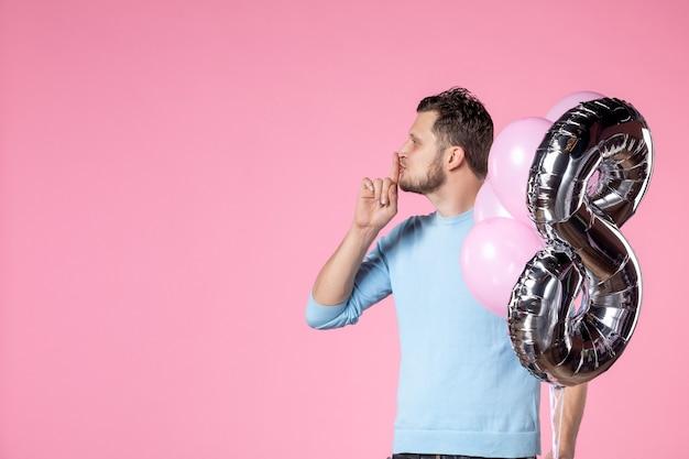 Вид спереди молодой мужчина с милыми воздушными шарами как марш присутствует на розовом фоне любовь женский женский день брак равенство свидание парк чувственное веселье