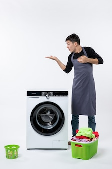 Front view of young male with dirty clothes and washer on white wall