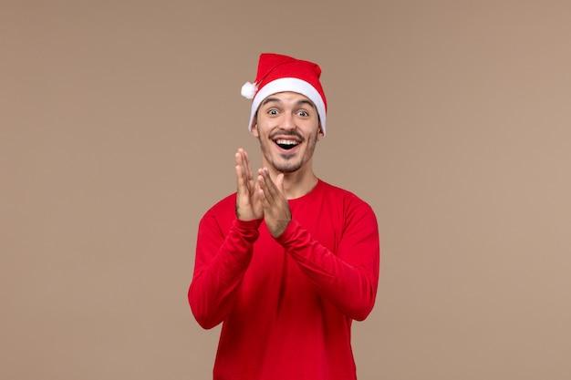 茶色の背景に興奮した表情の若い男性の正面図クリスマス感情休日