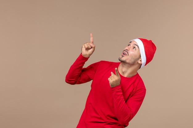 茶色の背景の感情のクリスマス休暇に興奮した表情で若い男性の正面図