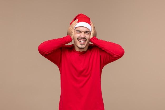 茶色の背景のクリスマス休暇の感情に興奮した表情で若い男性の正面図