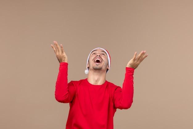 茶色の机の感情のクリスマス休暇に興奮した表情で若い男性の正面図