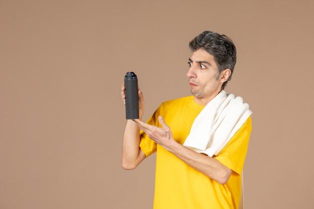 ピンクの背景に彼の顔を剃る準備をしている泡とタオルを持つ若い男性