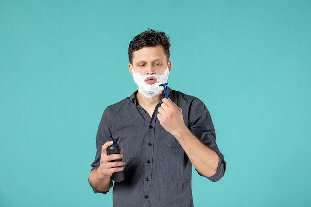 Front view young male with foam on his face preparing to shave on blue background