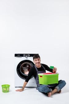 Vista frontale di un giovane maschio con cesto verde pieno di vestiti con carta di credito su muro bianco
