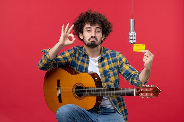 赤い壁のバンドの歌手のライブパフォーマンスミュージシャンコンサートのお金の色で銀行カードを保持しているギターを持つ若い男性の正面図